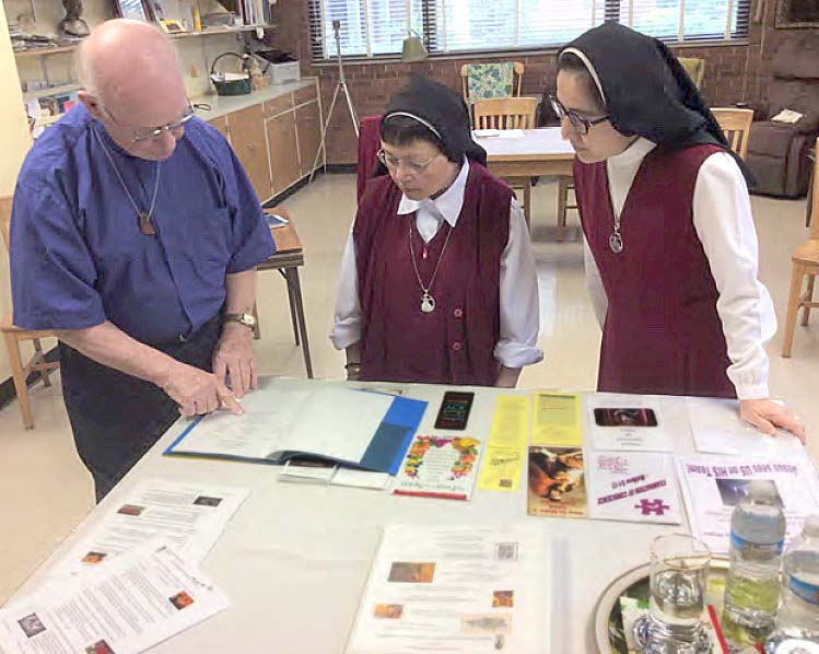 Fr. John Phelps reviews program materials with Sr. Maria Helena and Sr. Maria Celeste during the Day of Reflection.