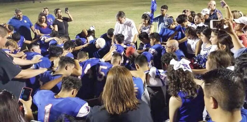 St. Gerard's High School football team taking a knee to pray.